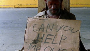 homeless person holding sign
